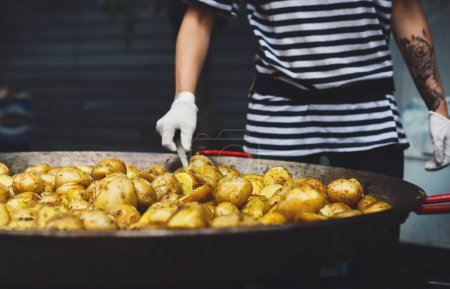 Photo for Country fair, vendor mix dish. Roasted potatoes cooked outdoors in big metal cauldron pot. Cookout vegetable meals. Fresh organic snack, potatoes cooked on grill flame. Street food, fast food. - Royalty Free Image
