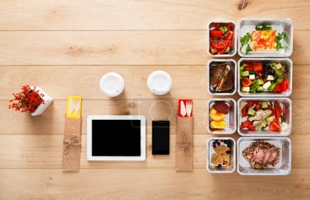 Photo for Online healthy restaurant food order, diet plan. Fresh daily meals delivery. Fitness nutrition, vegetable, meat and fruits in foil boxes, coffee and tablet. Top view, flat lay on wood with copy space - Royalty Free Image
