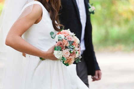 Wedding bouquet in bride hands standing next to groom