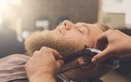 Barber styling beard at barbershop, closeup. Styli...