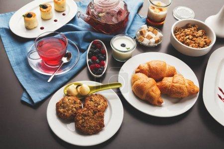 Photo for Sweet restaurant breakfast with oatmeal cookies, croissants, yogurt, cheese pancakes, muesli, fresh berries and freshly brewed tea served on black table. Nourishing morning meals - Royalty Free Image