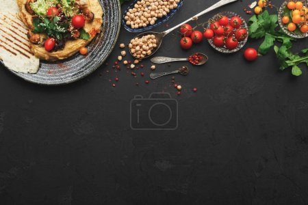 Photo for Chickpea hummus with mussels and vegetables in stylish bowl. Healthy traditional vegetarian beans pasta with olive oil and fresh pita bread served on black table background, top view, copy space - Royalty Free Image