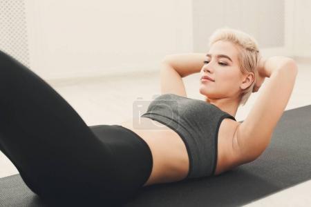 Photo pour Femme de remise en forme couché faire des croque à la salle de gym. Jeune fille sportive faisant assis sur le tapis. Mode de vie sain, gymnastique, concept de perte de poids - image libre de droit