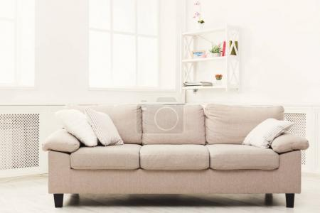 Photo for Beige couch with pillows in white modern interior, copy space on window background. Contemporary apartment design - Royalty Free Image