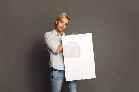 Photo for Young woman with blank white paper. Serious girl holding advertising sheet, copy space - Royalty Free Image