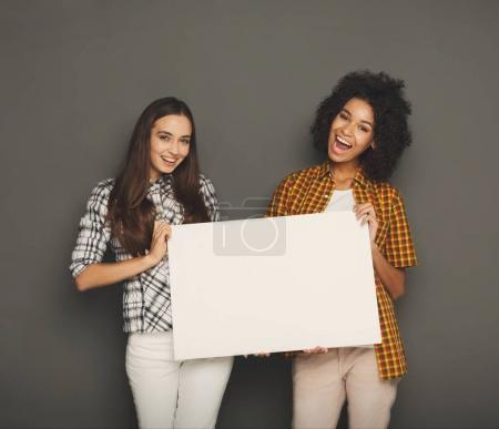 Photo for Multiethnic girls holding blank white banner with copy space on gray studio background - Royalty Free Image