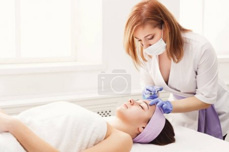 Photo for Woman gets beauty facial injections. Anti-aging, nourishing, vitamins treatment at spa salon. Aesthetic cosmetology - Royalty Free Image