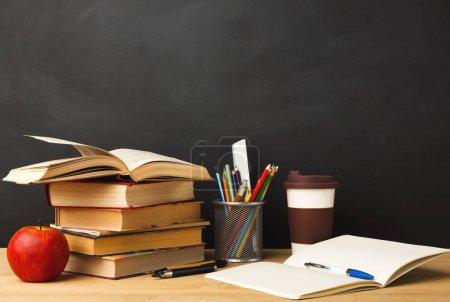 Photo pour Une formation. Les livres empilent, crayons, pomme, prendre une tasse de café et un carnet ouvert contre le tableau noir vide de la salle de classe pour l'espace de copie. Concept de retour à l'école - image libre de droit