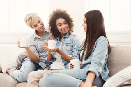 Photo for Three happy young female friends with coffee cups talking in living room at home, chatting about their life and relations, gossip and slumber party concept, copy space - Royalty Free Image