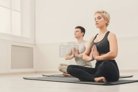Photo for Attractive couple practicing yoga sitting in padmasana. Young man and woman in lotus pose, namaste with closed eyes on mat at sport club interior, copy space - Royalty Free Image