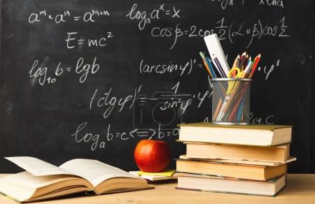 Photo for Studying mathematics educational background. Books pile, pencils and apple against classroom blackboard with chalk writing of sums. Back to school, research concept - Royalty Free Image