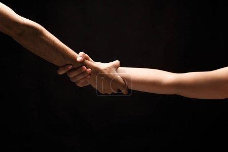 Photo pour Mains mâles et femelles serrées ensemble sur fond noir isolé. Amour, relations, soutien, ensemble pour toujours concept. Espace de copie, découpe, discret - image libre de droit