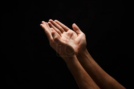 Photo for Outstretched male hands, man keeping empty cupped palms together isolated on studio black background - concept of charity, support, protection and care, closeup, copy space, cutout - Royalty Free Image