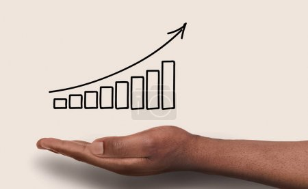 Photo for Conceptual business success background. African-american male hand over white backdrop with growth graph. Revenue, financial well-being and achievenment concept, copy space - Royalty Free Image