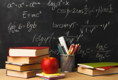 Photo pour Etudier les mathématiques formation. Livres pile, crayons et pomme contre tableau noir de classe avec écriture craie des sommes. Retour à l'école, concept de recherche - image libre de droit