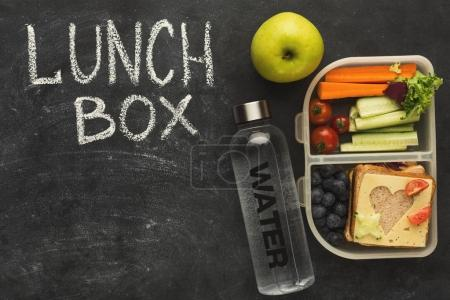 Photo for Eating right, storage and dieting conceptual background. Top view on assortment of healthy food in plastic containers on black chalk board with lunch box inscription and copy space - Royalty Free Image