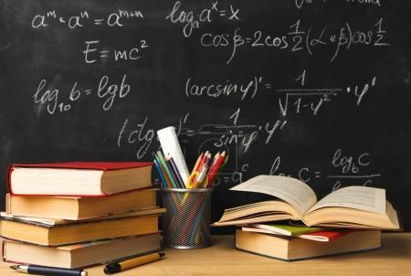 Photo pour Etudier les mathématiques formation. Les livres empilent, les crayons contre le tableau noir de la classe avec l'écriture craie des sommes. Retour à l'école, concept de recherche - image libre de droit