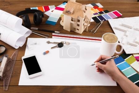 Photo pour Architecte projet architectural de dessin. Concepteur de méconnaissable mains travaillant avec blueprint, écran blanc smartphone, maquette de construction - image libre de droit