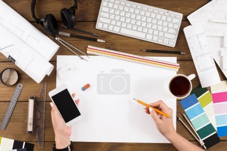 Photo for Architect drawing architectural project. Top view on unrecognizable designer hands working with blank building blueprint, blank smartphone screen, mockup - Royalty Free Image