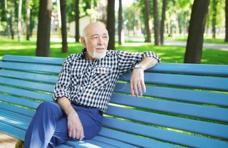 Photo pour Homme âgé souriant à l'extérieur. Homme âgé assis sur le banc dans le parc, espace de copie - image libre de droit