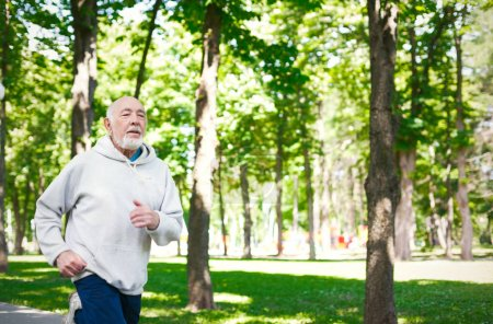 Photo for Elderly sporty man running in green park during morning workout, copy space. Healthy and active lifestyle at any age concept - Royalty Free Image