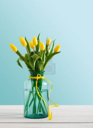 Photo for Yellow tulips on blue background, copy space. Bouquet of flowers in glass jar, mockup for mothers day, valentine or wedding greeting card - Royalty Free Image