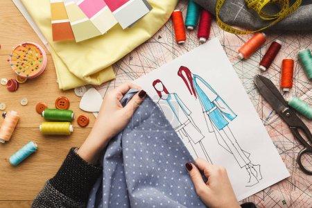 Foto de Vista superior del diseñador de moda trabajar con muestra material y croquis dibujado a mano en el fondo de la mesa desordenada, vista superior. Concepto de taller de confección, la creatividad y la costura - Imagen libre de derechos