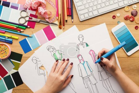 Photo for Top view on fashion designer at work. Female hands drawing clothes sketch at her creative workspace and using smartphone with blue gradient color swatches on screen, top view - Royalty Free Image