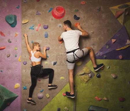 Photo pour Homme et femme heureux grimpeurs professionnels de remise en forme ayant l'entraînement à la salle de gym de bloc. Jeunes sportifs escaladant une paroi de roche artificielle, atteignant le sommet et le concept de soutien - image libre de droit