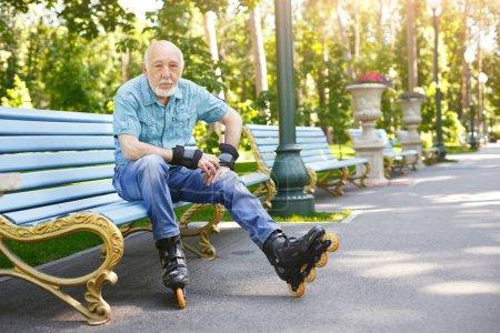 Photo pour Vieillesse active. Le sourire de vieil homme prêt à rollers au parc matin d'été. Mode de vie sain et sportif à toute notion de l'âge, espace copie - image libre de droit