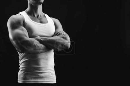 Photo for Strong athletic male, bodybuilder. Muscular body and strong shoulder muscles. Studio shot on black background, low key. Bodybuilding concept, black and white image - Royalty Free Image