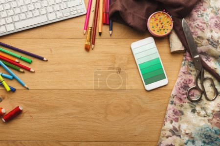 Foto de Vista superior del espacio de trabajo del diseñador de moda. Equipo, lápices de colores de costura portátil y móvil con degradado verde colorean muestras en pantalla en tabla de madera con espacio de copia - Imagen libre de derechos