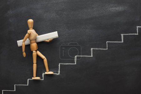 Photo for Wooden figure holding ruler and climbing step by step to the top of career and development stairs. Drawn stairs, copy space - Royalty Free Image