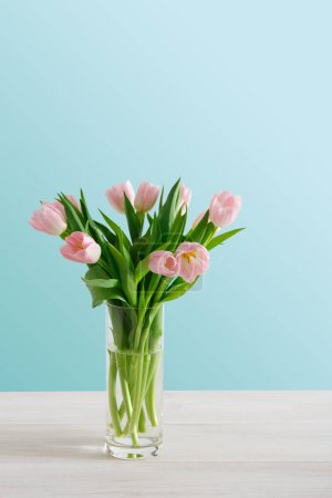 Photo for Tender pale pink tulips on blue background, copy space. Bouquet of flowers in glass jar, mockup for mothers day, valentine or wedding greeting card - Royalty Free Image