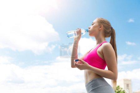 La corredora está descansando, bebiendo agua.