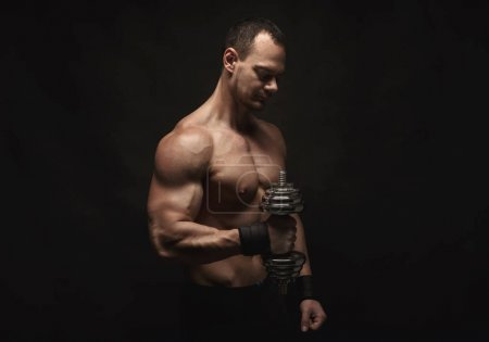 Photo for Athletic young man with a dumbbell on a black background. Naked torso, muscular body. Strong chest and shoulder muscles. Studio shot, low key. Bodybuilding concept, copy space - Royalty Free Image