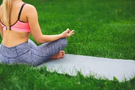 Photo for Young woman outdoors, meditation exercises, back view, crop. Girl does bufferfly pose for relaxation. Wellness, calmness, relax, healthy, active lifestyle concept - Royalty Free Image