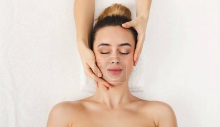 Photo for Facial massage. Spa, resort, beauty and health concept. Beautiful woman getting professional face treatment, top view, copy space - Royalty Free Image