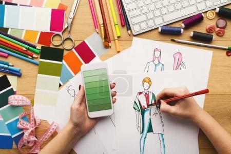 Foto de Vista superior de diseñador de moda en el trabajo. Mujer manos dibujo dibujo de ropa en su espacio de trabajo creativo y el uso de smartphone con muestras de color de degradado verde en la pantalla, vista superior - Imagen libre de derechos