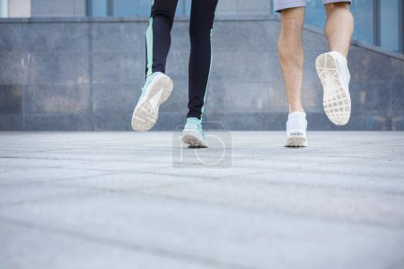 Photo for Male and female feet in sneakers. Couple running, crop, back view, copy space. Fitness, sport, foot wear and healthy lifestyle concept - Royalty Free Image