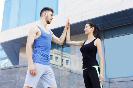 Sporty couple giving each other high five