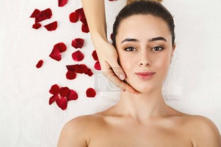 Photo for Woman enjoying anti aging facial massage. Pretty girl getting professional skin care at wellness center. Relaxation, beauty, spa and face treatment concept, top view, copy space - Royalty Free Image