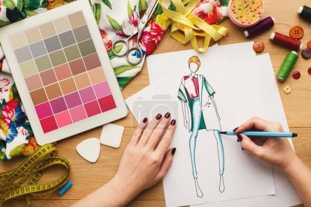 Foto de Vista superior de diseñador de moda en el trabajo. Mujer manos dibujo dibujo de ropa en su espacio de trabajo creativo y con tableta digital con muestras de color en pantalla, vista superior - Imagen libre de derechos