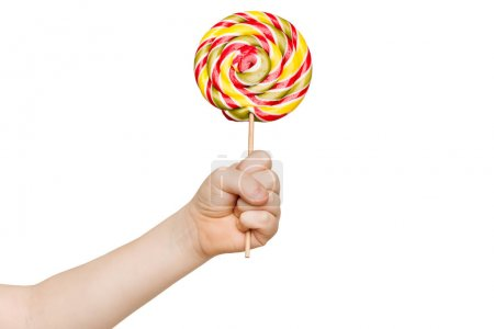 Photo for Childs hand holding big colorful lollipop candy on stick, isolated on white background. - Royalty Free Image