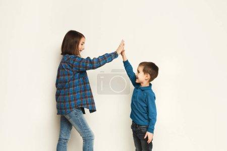 Photo pour Joyeux garçon et fille faisant cinq geste. fond studio blanc. Frère et sœur mignons célébrant leur succès - image libre de droit