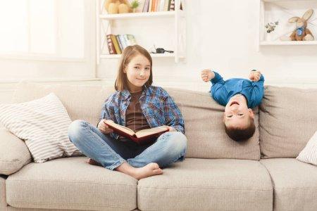 Photo pour Jeune fille lisant un livre à son frère. Sœur aînée racontant un conte de fées à haute voix, assise sur le canapé à la maison, espace de copie - image libre de droit