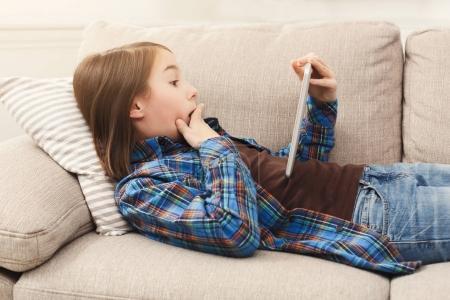 Photo pour Petite fille surprise utilisant une tablette numérique, allongée sur un canapé beige à la maison, espace de copie. Nouvelles choquantes, gagnant de loterie, concept de vente - image libre de droit