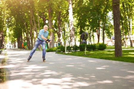 Photo pour Vieillesse active. Heureux homme senior rollers à l'extérieur. Vieil homme profiter des sports dans le parc ensoleillé de l'été. Concept de mode de vie sain, espace copie - image libre de droit