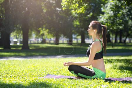 Photo for Young woman outdoors, meditation exercises. Girl doing lotus pose for relaxation with closed eyes and listening to music. Wellness, calmness, relax, healthy, active lifestyle concept, side view - Royalty Free Image
