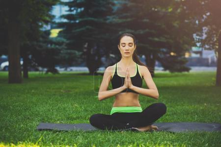 Photo for Attractive girl practicing yoga sitting in padmasana. Young woman in lotus pose, namaste with closed eyes on mat outdoors, copy space. Wellness, calmness, relax, healthy, active lifestyle concept - Royalty Free Image